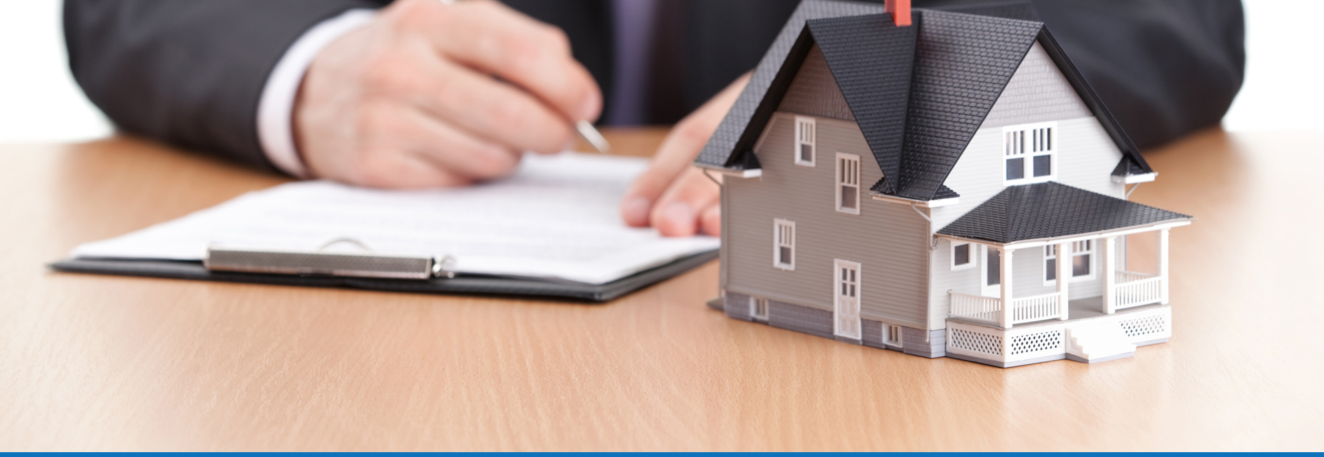 About Perfect Agent. Person signing real estate contract on table, behind a small house.