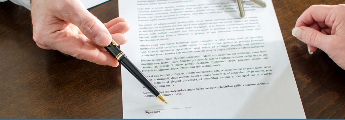Person signing real estate contract with a pen.