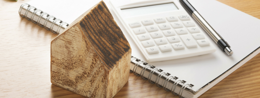 Small wooden carved house sitting on a desk with a a calculator and a noted pad with a book.