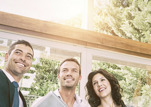 A real estate agent standing with two clients a man and a woman. Smiling and pointing to the house.