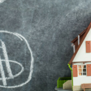 Shows dollar signs on black board next to 3d model home