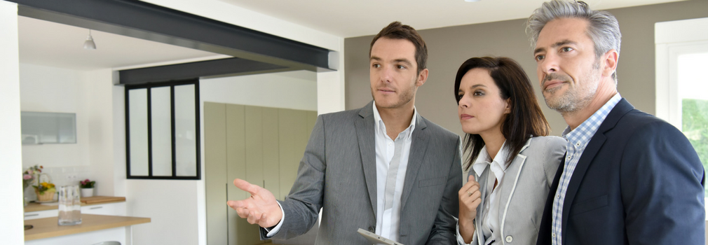 Couple standing with a real estate agent in a house.