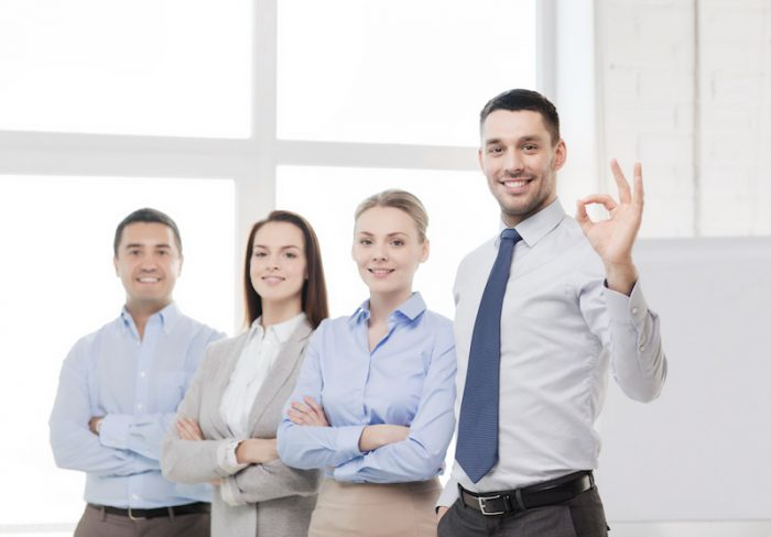 smiling real estate agent showing ok-sign in office
