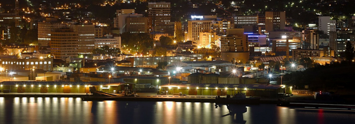 View of Hobart from across the river at night. You can see the lights of the city reflecting on the water.