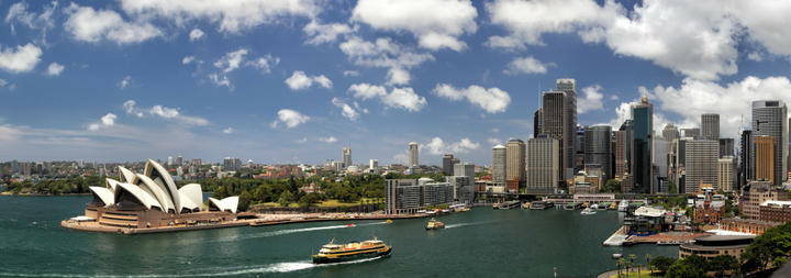 Sydney, Australia, Coastline with skyline view of the city. Boat in water blue skies and clouds.