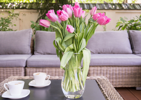 Modern patio, with grey patio set. Two cups on the table and a vase with flowers.