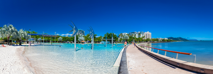 CAIRNS, AUSTRALIA. The Esplanade in Cairns with a jetty and the sea. Palm trees. white sandy beach. With building is the far background.