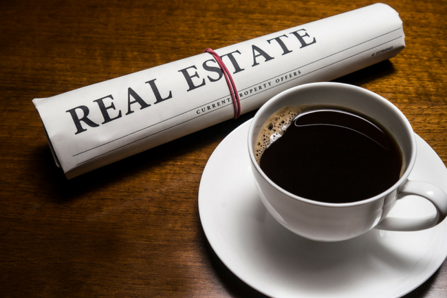 Cup of coffee on a dark wood table with a news paper on the table with the wording REAL ESTATE