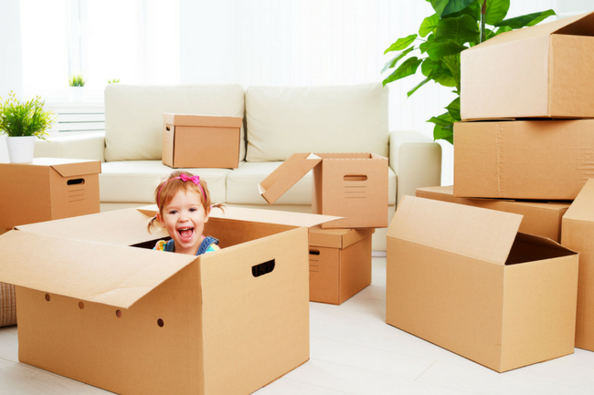 Room filled with light brown moving boxes. Small little girl with a big smile in one of the boxes.