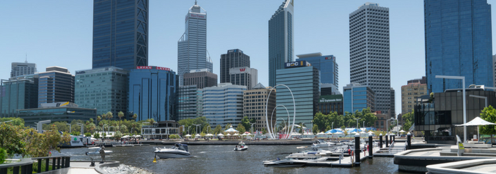 Skyline of Perth at the harbor, boats in the water, buildings in the background.