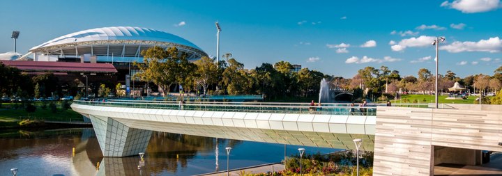 Adelaide Oval and foot bridge viewed across Elder Park on a bright day