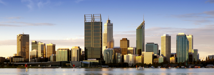 Image of Perth at dusk, highrise buildings in the back ground, with a clear blue sky.